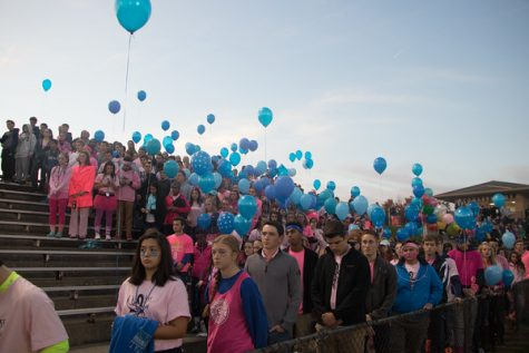 Students wear pink to support middle school teacher Colleen Pringle and hold blue balloons for Evan Thompson during a moment of silence at the home football game against Williamston Oct. 14.